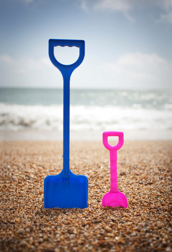 Blue and pink spades standing in sand at beach
